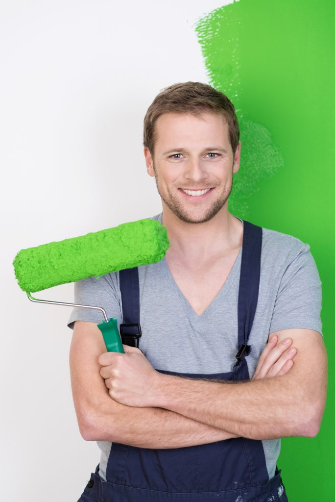 painter holding brush preparing for home wall painting service while smiling